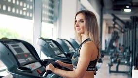Jonge geschikte vrouw die lopende oefening in gymnastiek doen stock videobeelden
