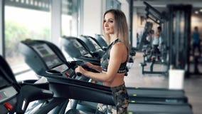 Jonge geschikte vrouw die lopende oefening in gymnastiek doen stock video