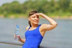 Jonge geschikte vrouw die na jogging door de rivier in stad rusten Hand Royalty-vrije Stock Fotografie
