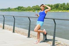 Jonge geschikte vrouw die na jogging door de rivier in stad rusten Hand Stock Foto's