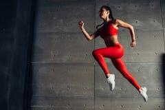 Jonge geschikte vrouw die terwijl het runnen van Fitness sportmeisje het uitoefenen springen royalty-vrije stock fotografie