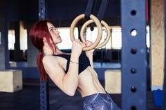 Jonge geschikte vrouw die trekkracht-UPS op gymnastiek- ringen doen Stock Afbeeldingen