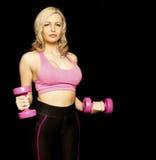 Jonge geschikte vrouw die vrije gewichten houden Stock Afbeeldingen
