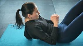 Jonge geschikte vrouwen bij de gymnastiek die abs training op een mat, een gezond levensstijl en een geschiktheidsconcept doen stock footage