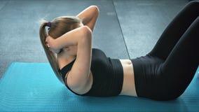 Jonge geschikte vrouwen bij de gymnastiek die abs training op een mat, een gezond levensstijl en een geschiktheidsconcept doen stock videobeelden