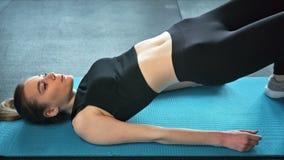 Jonge geschikte vrouwen bij de gymnastiek die abs training op een mat, een gezond levensstijl en een geschiktheidsconcept doen stock video