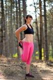 Jonge Geschiktheidsvrouw die haar Benen in de Pijnboom Forest Female Runner Doing Stretches uitrekken Gezond levensstijlconcept Stock Foto's