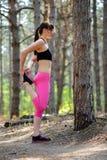 Jonge Geschiktheidsvrouw die haar Benen in de Pijnboom Forest Female Runner Doing Stretches uitrekken Gezond levensstijlconcept Stock Afbeeldingen