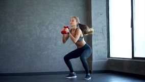 Jonge geschiktheidsvrouw die hurkzit met domoren in handen doen Scène in de gymnastiek stock video