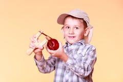 Jonge geschotene de spruitappel van het jongensgebruik slinger Royalty-vrije Stock Afbeeldingen