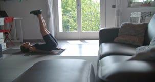 Jonge getatoeeerde vrouw die krakenoefening het uitrekken thuis doen zich tijdens fitness sporttraining Binnenlandse woonkamer stock videobeelden