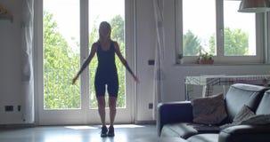 Jonge getatoeeerde vrouw die springende hefbomenoefening doen tijdens huisfitness sporttraining Woonkamer binnenlandse opleiding  stock footage
