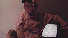 Jonge getatoeeerde vrouwenzitting die dichtbij statische TV-reeks in donkere ruimte werken stock videobeelden