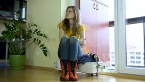 Jonge gezette vrouw, GLB bij het zitten op koude radiator stock videobeelden