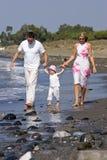 Jonge, gezonde familie die langs een zonnig strand lopen stock fotografie