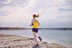Jonge gezonde levensstijlvrouw die bij zonsopgangstrand lopen Stock Foto's