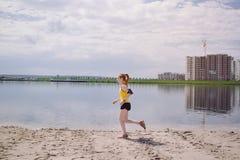 Jonge gezonde levensstijlvrouw die bij zonsopgangstrand lopen Royalty-vrije Stock Foto's