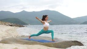 Jonge gezonde sportieve vrouw het praktizeren yoga op het strand bij zonsondergang stock videobeelden