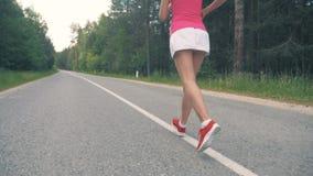 Jonge gezonde vrouw die langs de weg lopen Gezond levensstijlconcept stock footage