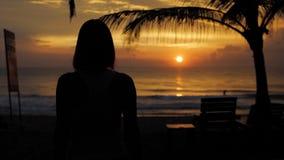 Jonge gezonde vrouw het praktizeren yoga op het strand bij zonsondergang oceaangolven Sterke vertrouwensvrouw onder de zonsonderg stock video