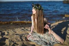 Jonge gezonde vrouw het praktizeren yoga op het strand bij zonsopgang royalty-vrije stock afbeelding