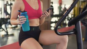Jonge gezonde vrouwelijke berijdende hometrainer en het scrollen geschiktheid app op cellphone stock video