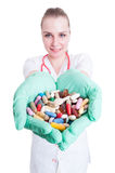 Jonge glimlachende arts die vele pillen in haar palmen houden royalty-vrije stock foto's