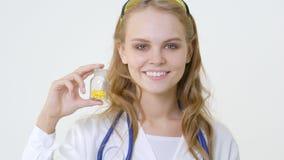 Jonge glimlachende arts met kruik van capsules Vriendschappelijke vrouwelijke arts stock footage