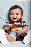 Jonge glimlachende baby met stuk speelgoed Royalty-vrije Stock Foto's