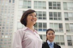Jonge glimlachende bedrijfsvrouwen die zich buiten CBD, portret bevinden Royalty-vrije Stock Afbeeldingen