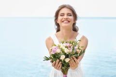 Jonge glimlachende bruid in het witte boeket van de togaholding Royalty-vrije Stock Foto