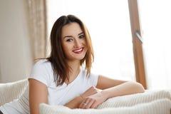 Jonge glimlachende dame met mooie samenstelling zitting en het ontspannen op de bank Royalty-vrije Stock Afbeeldingen