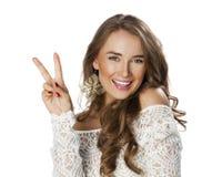Jonge glimlachende donkerbruine vrouw die overwinning of vredesteken tonen Stock Afbeeldingen