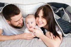 Jonge glimlachende familie met zuigeling onder deken royalty-vrije stock afbeeldingen