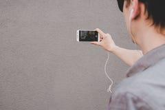 Jonge glimlachende hipster mens die selfie met zijn smartphone nemen en het bekijken camera met aandacht stock foto