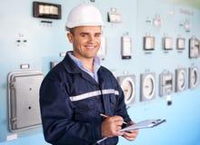 Jonge glimlachende ingenieur die nota's nemen bij controlekamer Stock Afbeeldingen