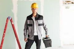 Jonge glimlachende ingenieur in het werkkleren en gele bouwvakker holdin stock afbeelding