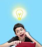 Jonge glimlachende jongen met één hand die op wang met toespraakbel tegen blauwe achtergrond rusten Stock Foto