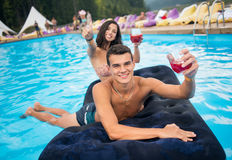 Jonge glimlachende man met cocktails die op een opblaasbare matras in pool met vrouw uit nadruk naast hem liggen royalty-vrije stock foto