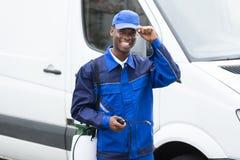 Jonge Glimlachende Mannelijke Arbeider met Pesticidespuitbus stock afbeelding