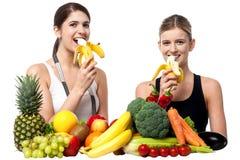 Jonge glimlachende meisjes die banaan eten Stock Afbeelding