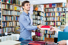Jonge glimlachende mens die gekozen boek van verkoper nemen royalty-vrije stock foto