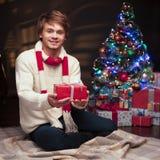 Jonge glimlachende mens die rode Kerstmisgift houdt Stock Afbeelding