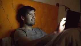 Jonge glimlachende mens die tabletcomputer voor het surfen sociale media met behulp van die in bed thuis vóór slaap liggen stock videobeelden