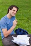 Jonge glimlachende mens die terwijl het zitten op het gras werkt Royalty-vrije Stock Foto's