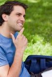 Jonge glimlachende mens die zijn vinger plaatst op zijn kin Stock Fotografie
