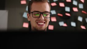Jonge glimlachende mens in glazen die bij laptop in het bureau werken Zakenman - beambte Het mannelijke studentenwerk bij a stock video