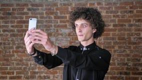 Jonge glimlachende mens met krullend haar die selfie nemen en zich dichtbij bakstenen muur, gelukkige uitdrukking bevinden stock videobeelden