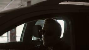 Jonge glimlachende mens in zonnebril die auto drijven De mannelijke zitting binnen, omgekeerde en opent het autoraam op de parker stock video
