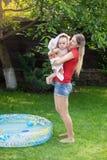 Jonge glimlachende moeder die haar zoon van de 10 maanden oudbaby na het zwemmen in openlucht opblaasbaar zwembad afvegen Stock Fotografie